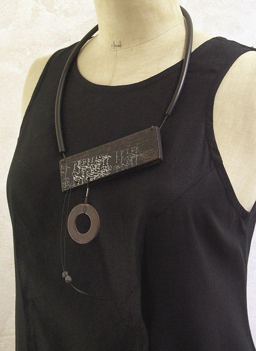 Necklace made of ebony, hand written paper, oxidized iron, rubber Joyas